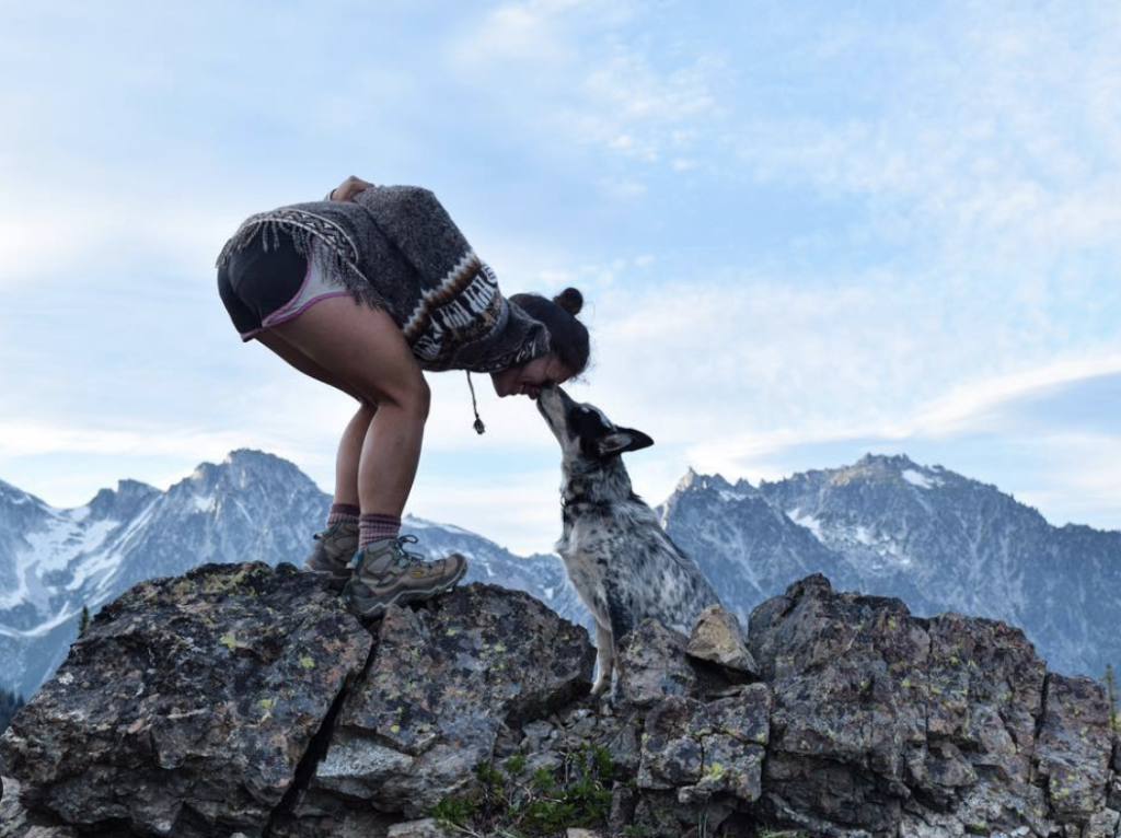 Person crouching down to kiss dog on mountain